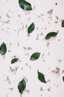 Fleurs lilas et feuilles sur une surface en bois blanche