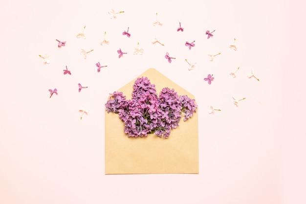 Fleurs de lilas pourpre avec du papier vierge sur la table. style rustique.
