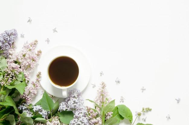 Fleurs lilas avec tasse de café. fleurs de printemps. vue de dessus, mise à plat, espace de copie.