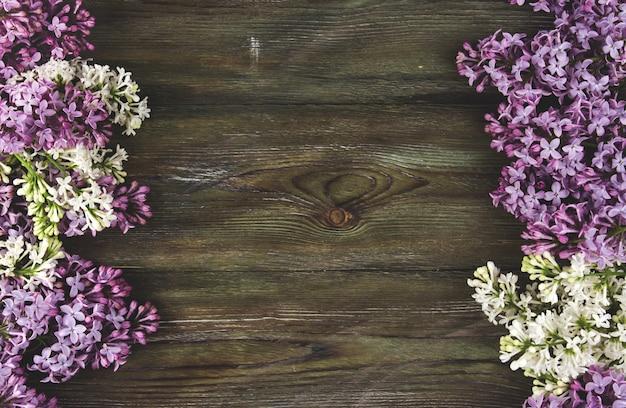 Fleurs lilas sur un vieux fond en bois. une bordure de fleurs lilas copie l'espace.