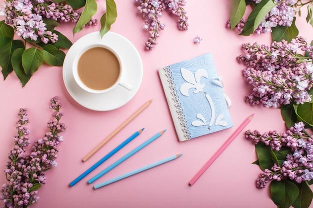 Fleurs lilas violettes et une tasse de café avec cahier et crayons de couleur