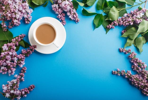 Fleurs lilas violettes et une tasse de café sur du bleu pastel.