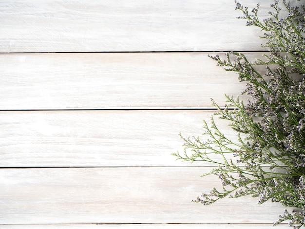 Fleurs de limonium mauve sur fond en bois blanc