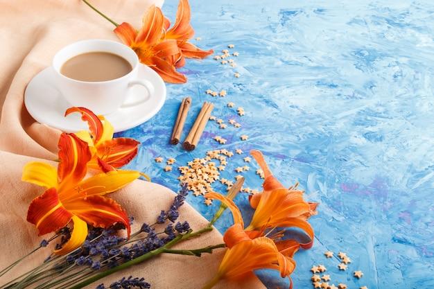 Fleurs de lis du jour et de lavande orange et une tasse de café sur un fond de béton bleu, avec du textile orange. vue de côté.