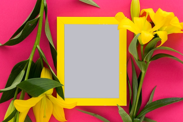 Fleurs de lis jaune et cadre d'image vide au-dessus du rose; contexte