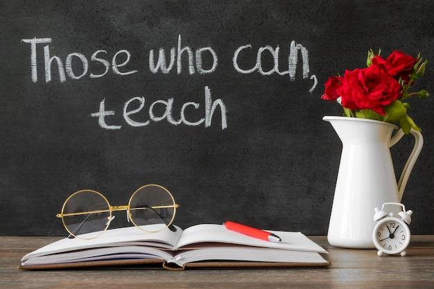 Fleurs et livre concept de jour de professeur heureux