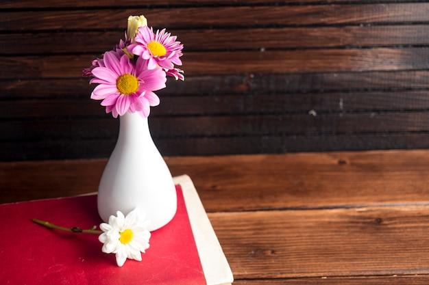 Fleurs lumineuses dans un vase blanc sur un livre