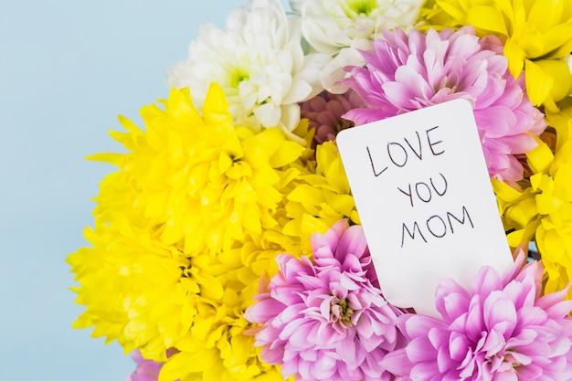 Fleurs lumineuses fraîches avec étiquette avec titre de maman