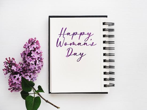 Fleurs lumineuses et lettrage happy women's day. gros plan, pas de monde, texture. félicitations à la famille, aux parents, aux amis et aux collègues