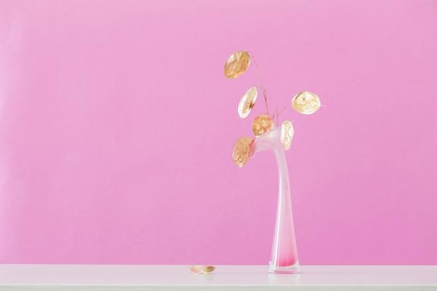 Fleurs de lune séchées dorées dans un vase sur fond rose