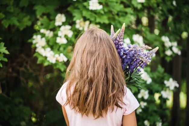Fleurs de lupin entre les mains des filles, beauté, confection de bouquets de plantes différentes, jardinage, enfance, intérieur, champ