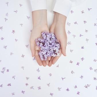 Fleurs de lys de printemps dans les mains d'une femme allongée sur une table blanche. cosmétiques naturels pour les mains, mains anti-rides. beauté naturelle d'une femme