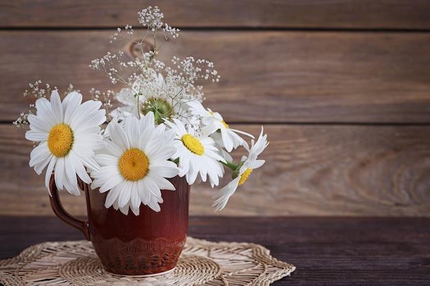 Fleurs de marguerite sauvage blanche dans un vase sur l'ancienne table