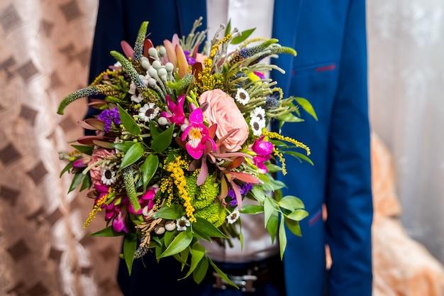 Fleurs de mariage pour un événement spécial, fermer u vue du marié tenant un bouquet de fleurs à la main