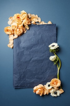 Fleurs et un morceau de papier noir dans un cadre avec un espace pour le texte sur fond sombre, mise à plat