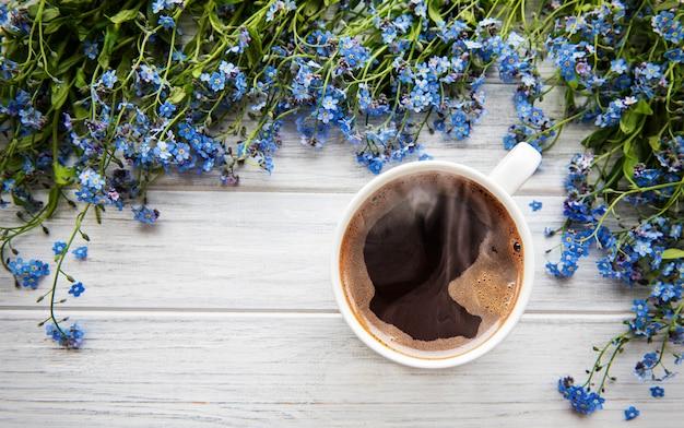 Fleurs de myosotis et tasse de café sur un fond en bois