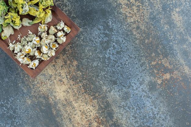 Fleurs naturelles séchées sur planche de bois.
