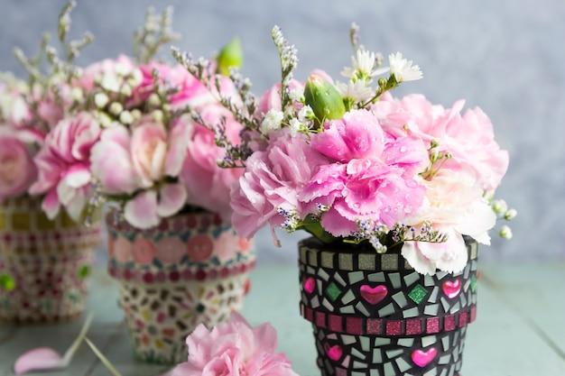 Fleurs d'oeillets en pot de fleurs de mosaïque sur le vieux bois