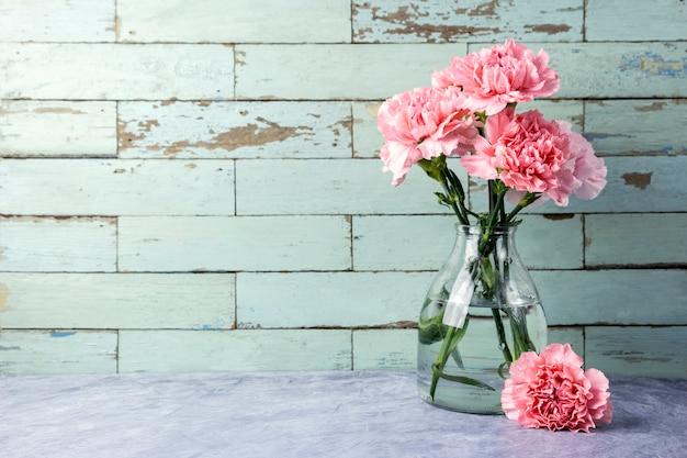 Fleurs d'oeillets roses en bouteille de verre avec espace copie