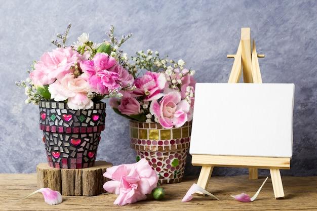 Fleurs d'oeillets roses dans un pot de fleurs de mosaïque et cadre de toile blanche sur la peinture de chevalet