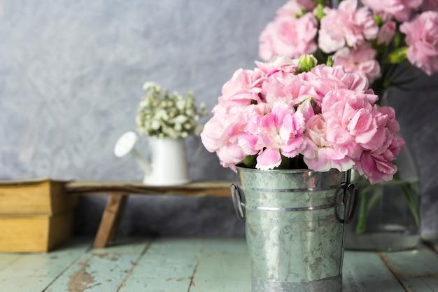 Fleurs d'oeillets roses en seau de zinc sur bois de table