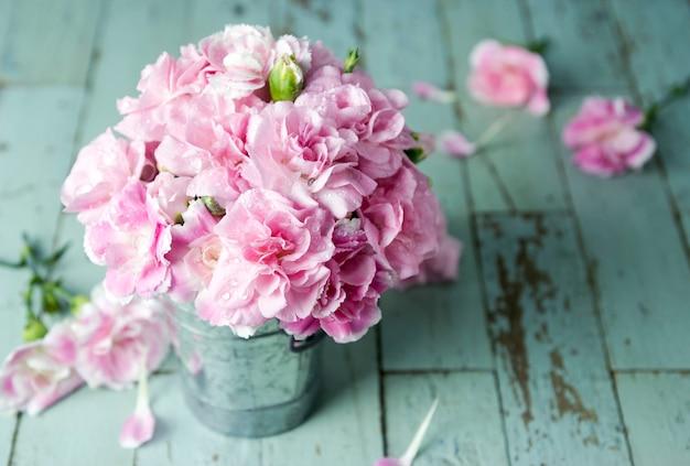 Fleurs d'oeillets roses en seau de zinc sur bois vintage