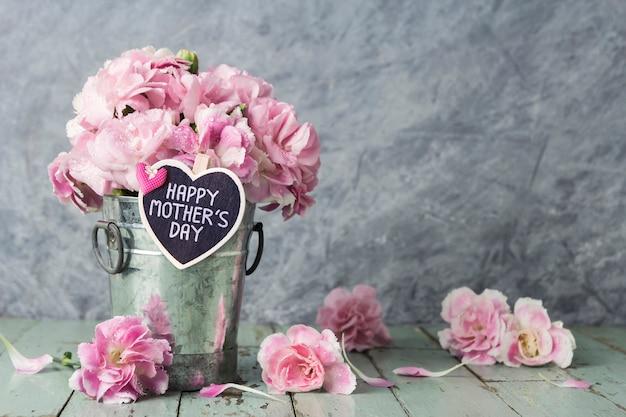 Fleurs d'oeillets roses en seau de zinc avec la lettre de la bonne fête des mères sur coeur de bois