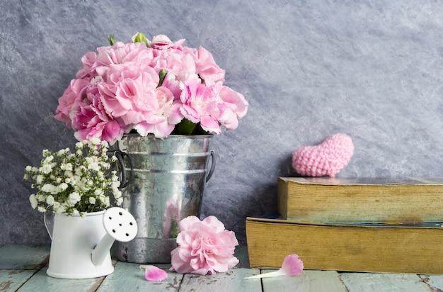 Fleurs d'oeillets roses en seau de zinc et livre sur le vieux bois