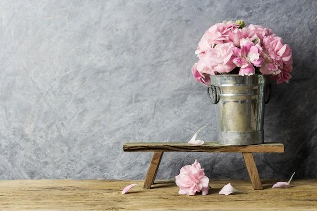 Fleurs d'oeillets roses en seau de zinc sur le vieux bois