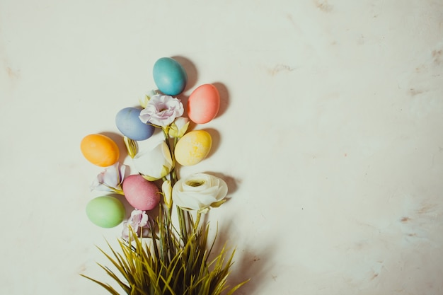 Fleurs et oeufs sur fond rose mable, copiez l'espace pour les salutations de pâques
