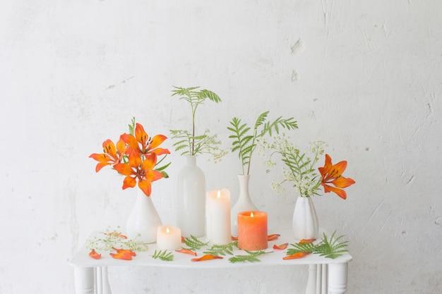 Fleurs orange et bougies sur fond blanc