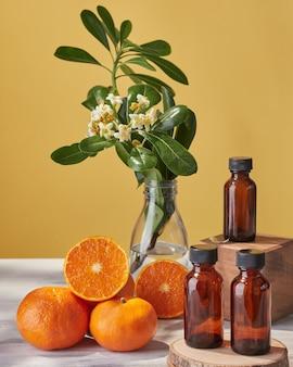 Fleurs d'oranger et mandarines fraîches coupées en deux et à côté de petites bouteilles en verre foncé vides