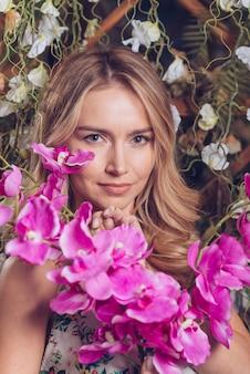 Fleurs d'orchidée fraîches exotiques devant une jeune femme blonde