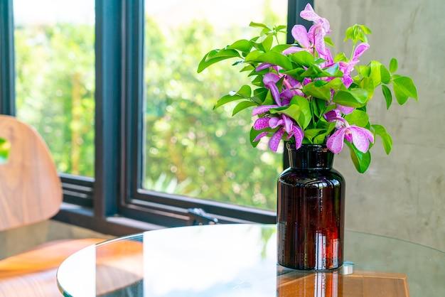 Fleurs d'orchidées dans la décoration de vase sur la table dans un café restaurant café