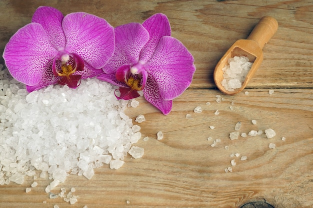 Fleurs d'orchidées sur un fond en bois avec du sel de mer blanc pour le corps