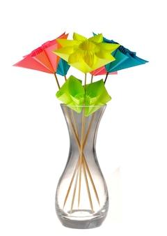 Fleurs d'origami dans un vase en verre isolé sur blanc.