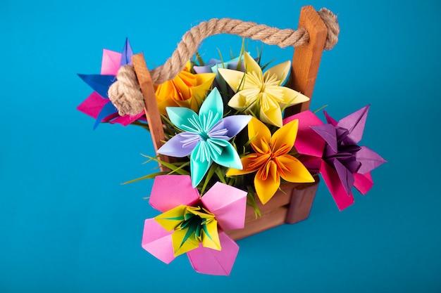 Fleurs en papier de couleur à la main origami bouquet artisanat en papier dans un panier avec de l'herbe en studio sur fond aqua coloré