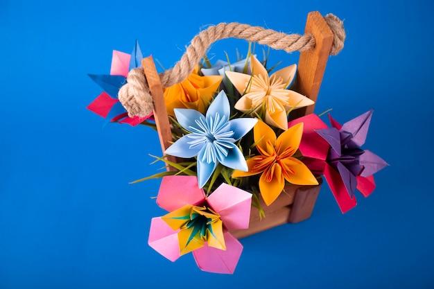 Fleurs en papier de couleur à la main origami bouquet artisanat en papier dans un panier avec de l'herbe en studio sur fond bleu coloré