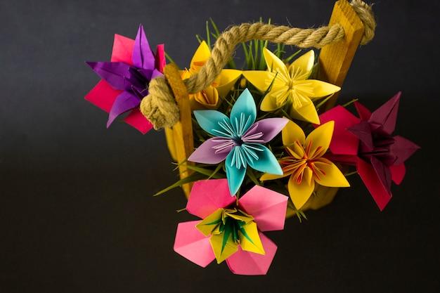 Fleurs en papier de couleur à la main origami bouquet papier artisanat art dans un panier avec de l'herbe en studio sur fond coloré topshot