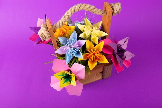 Fleurs en papier de couleur à la main origami bouquet papier artisanat art dans un panier avec de l'herbe en studio sur fond rose coloré