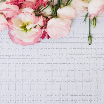 Fleurs sur papier avec graphique de battement de coeur