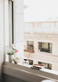 Fleurs par une bouteille de parfum sur un rebord de fenêtre