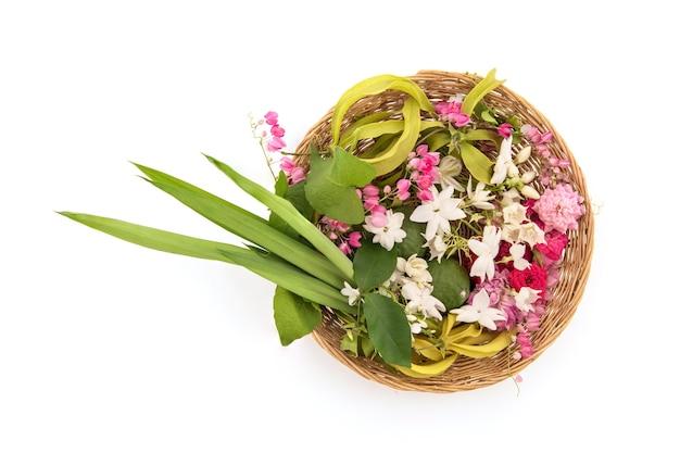 Fleurs parfumées telles que la fleur d'ylang-ylang, la rose, le jasmin et les feuilles vertes de pandanus isolées.vue de dessus, pose à plat.