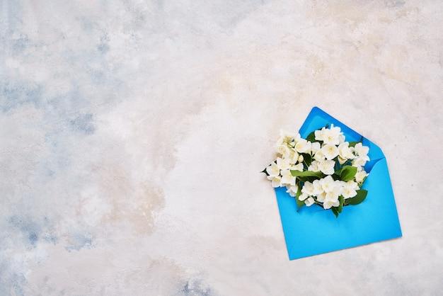 Fleurs de philadelphus ou de faux-orange dans une enveloppe violette. mise à plat