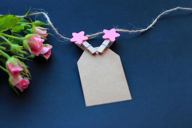 Fleurs, pinces à linge décoratives et papier pour les notes sur fond sombre. concept de félicitations pour les vacances