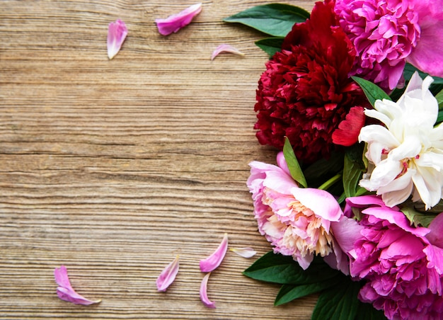 Fleurs de pivoine rose sur une vieille table en bois