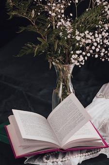 Fleurs avec des plantes dans un vase près du livre et des perles sur du textile blanc