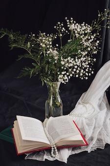 Fleurs avec des plantes dans un vase près du volume et des perles sur du textile blanc