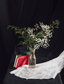 Fleurs avec plantes dans un vase près de volumes et perles sur textile blanc sur table