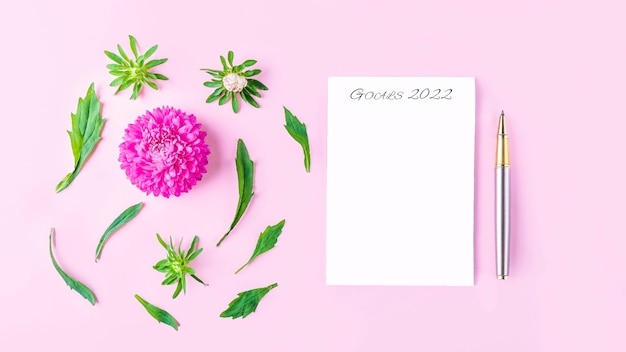 Fleurs à plat, nature morte romantique. cahier vide avec espace de copie pour texte, objectifs ou défi aujourd'hui et fleurs roses. lieu de travail de femme indépendante. carte de voeux d'invitation.